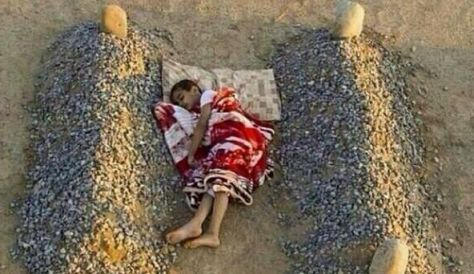 a young Syrian child sleeping next to the graves of his dead parents