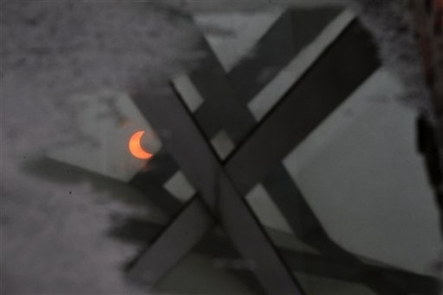 The eclipse is reflected in a pool of water in Beijing, China