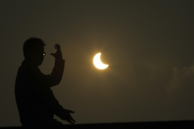 A man practices taichi during an eclipse at the Bund along the Huangpu River in Shanghai
